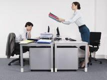 Männlicher Kollege Geschäftsfrau-Passing Folders Tos im Büro stockfoto