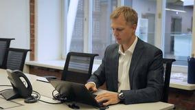 Männlicher Kopf funktioniert am Schreibtisch mit dem Laptop, der im modernen Büro sitzt stock footage
