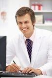 Männlicher Krankenhausdoktor am Schreibtisch Stockbild