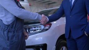 Männlicher Kunde überreicht Autoschlüssel zum Automechaniker für Reparatur und rüttelt Hände auf Hintergrund des Automobils am Se stock video footage