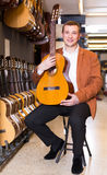Männlicher Kunde, der auf Akustikgitarre im musikalischen Shop entscheidet Lizenzfreie Stockfotografie