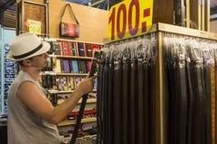 Männlicher Kunde, der Gurt im Marktstand, Hua Hin wählt Lizenzfreie Stockfotografie
