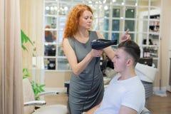 Männlicher Kunde, der Haarschnitt erhält Mädchenfriseur trocknet mein Haar ein junger, attraktiver Kerl in einem Schönheitssalon lizenzfreies stockbild