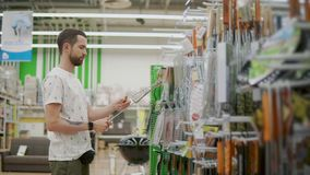Männlicher Kunde nimmt Gitter für Grill in einem Shop und überprüft es stock video