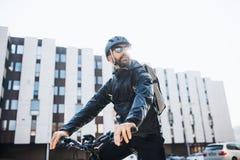 Männlicher Kurier mit dem Fahrrad und Sonnenbrille, die Pakete in der Stadt liefern lizenzfreie stockbilder