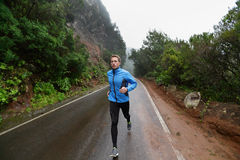 Männlicher Läufer, der auf Straße in der Natur rüttelt und läuft stockbilder