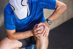 Männlicher Läufer, der Probleme im Knie hat stockfotografie