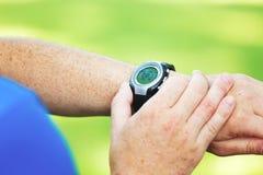 Männlicher Läufer, der Uhr betrachtet stockfotos