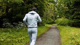 Männlicher Läufer in der warmen Kleidung im Herbstpark hörend auf Musik und Haubenkleidung stock footage