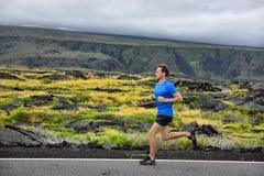 Männlicher Läufer des Athleten, der auf Gebirgsstraße läuft stockbild