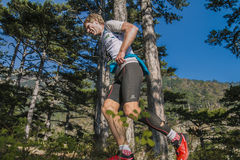 Männlicher Läufer des Mittelalters läuft durch Kiefernwald Lizenzfreies Stockfoto