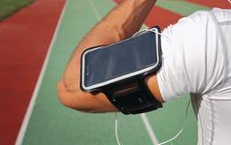 Männlicher Läufer mit dem intelligenten Mobiltelefon, hörend Musik während des Trainings Laufen, Rütteln, Herz, Sport, aktiver Le Lizenzfreie Stockfotos