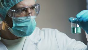 Männlicher Laborassistent, der flüssige Probe, Experimente auf Haushaltschemikalien betrachtet stock footage