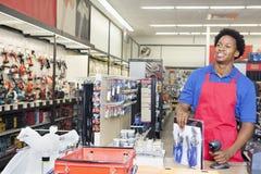 Männlicher Ladenangestellter des Afroamerikaners an der Kasse im Supermarkt Lizenzfreies Stockfoto