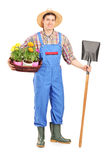 Männlicher Landarbeiter, der eine Schaufel und Blumen hält Stockfoto