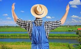 Männlicher Landwirt, der mit den angehobenen Händen gestikuliert Stockfoto