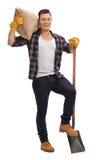 Männlicher Landwirt, der mit einer Schaufel und einem Sack aufwirft Stockfotos