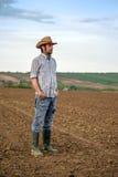 Männlicher Landwirt Standing auf fruchtbarem landwirtschaftlichem Ackerland-Boden Stockfotografie