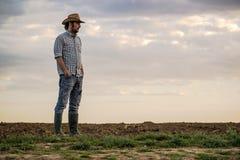 Männlicher Landwirt Standing auf fruchtbarem landwirtschaftlichem Ackerland-Boden Lizenzfreies Stockfoto