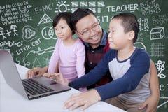 Männlicher Lehrer, der einen Laptop mit seinen Studenten verwendet Lizenzfreies Stockfoto