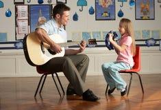 Männlicher Lehrer, der Gitarre mit Pupille in Classroo spielt Lizenzfreie Stockfotografie
