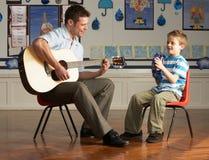 Männlicher Lehrer, der Gitarre mit Pupille in Classroo spielt stockfotografie