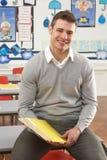 Männlicher Lehrer, der am Schreibtisch im Klassenzimmer sitzt Lizenzfreies Stockfoto