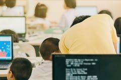 Männlicher Lehrer gelbes Hemd in umhergehender Klasse, in Helfen und in che lizenzfreies stockbild