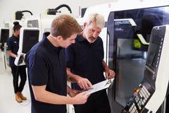 Männlicher Lehrling, der mit Ingenieur-On CNC-Maschinerie arbeitet stockbilder