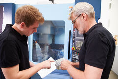 Männlicher Lehrling, der mit Ingenieur-On CNC-Maschinerie arbeitet stockfotos