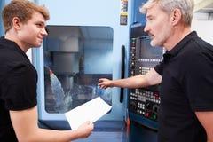 Männlicher Lehrling, der mit Ingenieur-On CNC-Maschinerie arbeitet lizenzfreies stockbild