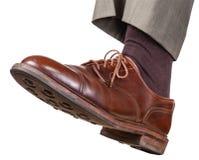 Männlicher linker Fuß im braunen Schuh unternimmt einen Schritt Lizenzfreies Stockbild