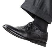 Männlicher linker Fuß im schwarzen Schuh unternimmt einen Schritt Lizenzfreie Stockbilder
