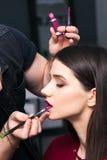 Männlicher Make-upkünstler Colors das Lippenbrunettemädchen im Schönheitssalon, Nahaufnahme Lizenzfreie Stockfotos
