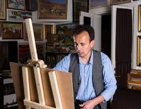 Männlicher Maler gerichtet auf das Malen seines Bildes Stockfoto