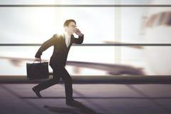 Männlicher Manager, der auf dem Flughafenabfertigungsgebäude läuft stockbild