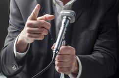 Männlicher Manager, der mit einem Mikrofon mit Handzeichen spricht Lizenzfreie Stockbilder