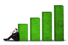 Männlicher Manager, der mit Wachstumsgeschäftsdiagramm sitzt stockfotos