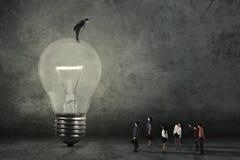 Männlicher Manager mit Lampe und seinen Arbeitskräften Stockbilder