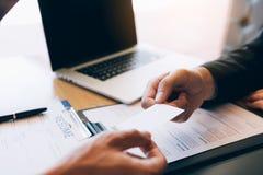 Männlicher Manager reicht die Visitenkarte beim Angestellten ein, um mit dem Vorstellungsgespräch in Verbindung zu treten lizenzfreie stockbilder