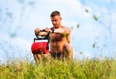 Männlicher Mann, der draußen mit einem Gewicht trainiert stockbilder