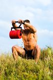 Männlicher Mann, der draußen mit einem Gewicht trainiert stockfotografie