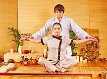 Männlicher Masseur, der Massagefrau im Bambusbadekurort tut. Stockfotografie