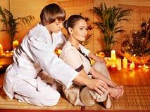 Männlicher Masseur, der Massagefrau im Bambusbadekurort tut. Stockfoto