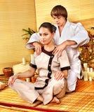 Männlicher Masseur, der Massagefrau im Bambusbadekurort tut. Lizenzfreie Stockfotografie