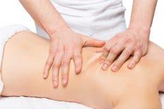 Männlicher Masseur tut Rückenmassage auf einer Tabelle stockfoto