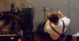 Männlicher Mechaniker, der Autoreifen mit Kantenschlüssel 4k entfernt stock video footage