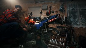 Männlicher Mechaniker, der ein Motorrad in der Garage repariert stock video footage