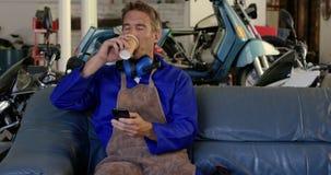 Männlicher Mechaniker, der Handy in der Motorradreparaturgarage 4k verwendet stock video footage