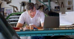 Männlicher Mechaniker, der Kaffee beim 4k bei Tisch schreiben trinkt stock footage